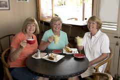 Groupe de trois amies mûres supérieures de femmes de beau Moyen Âge se réunissant pour le café et le thé avec des gâteaux au café Image stock
