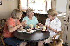 Groupe de trois amies mûres supérieures de femmes de beau Moyen Âge se réunissant pour le café et le thé avec des gâteaux au café Image libre de droits