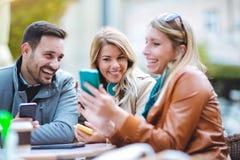 Groupe de trois amis à l'aide du téléphone en café extérieur Image stock