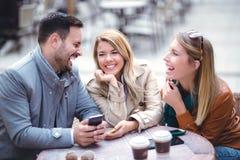 Groupe de trois amis à l'aide du téléphone en café extérieur Image libre de droits