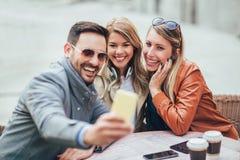 Groupe de trois amis à l'aide du téléphone en café extérieur photos libres de droits