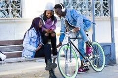 Groupe de trois amis à l'aide du téléphone portable dans la rue Photos libres de droits