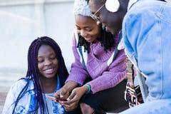 Groupe de trois amis à l'aide du téléphone portable dans la rue Images stock