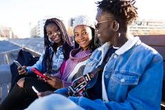 Groupe de trois amis à l'aide du téléphone portable dans la rue Images libres de droits