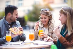 Groupe de trois amis en café extérieur le jour ensoleillé, Images stock