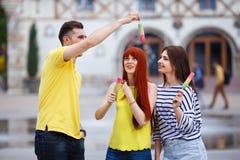 Groupe de trois amis marchant dans la ville mangeant la crème glacée, jok Photo libre de droits