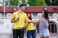 Groupe de trois amis marchant dans la ville mangeant la crème glacée, jok Image libre de droits