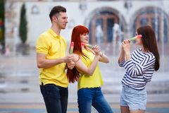 Groupe de trois amis marchant dans la ville mangeant la crème glacée, jok Photo stock