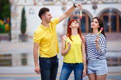 Groupe de trois amis marchant dans la ville mangeant la crème glacée, jok Image stock