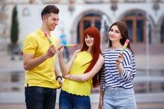 Groupe de trois amis marchant dans la ville mangeant la crème glacée, jok Images stock