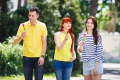 Groupe de trois amis marchant en parc mangeant la crème glacée  Photo stock