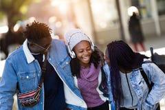 Groupe de trois amis marchant et riant dans la rue Photo stock