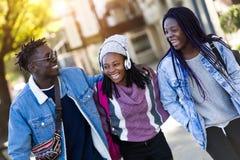 Groupe de trois amis marchant et riant dans la rue Images libres de droits