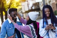 Groupe de trois amis marchant et riant dans la rue Photos libres de droits