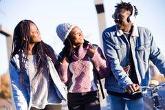 Groupe de trois amis marchant et riant dans la rue Photo libre de droits