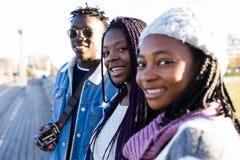 Groupe de trois amis regardant l'appareil-photo dans la rue Photos stock