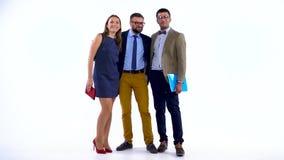 Groupe de trois associés posant dans le studio pour l'appareil-photo banque de vidéos