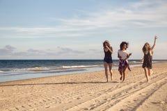 Groupe de trois belles jeunes femmes marchant sur la plage Photo libre de droits