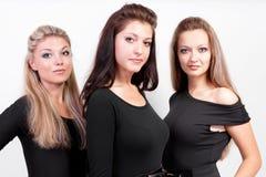 Groupe de trois dames dans des procès de fuselage noir Photographie stock libre de droits