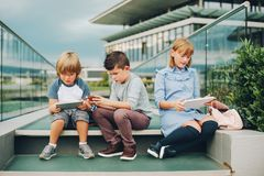 Groupe de trois enfants drôles utilisant des sacs à dos marchant de nouveau à l'école Image stock