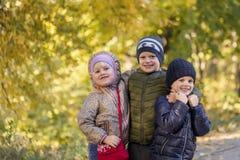 Groupe de trois enfants heureux ayant l'amusement dehors dans le parc d'automne Les enfants mignons ont plaisir à étreindre ensem Image libre de droits