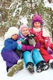 Groupe de trois filles d'enfants s'asseyant dans la neige ensemble Photos libres de droits