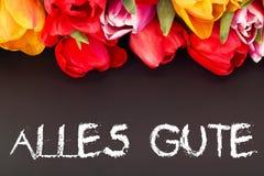 Groupe de tulipes avec le tableau noir : tout le meilleur dans la langue allemande Photos stock