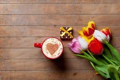 Groupe de tulipes, de cadeau et d'une tasse de café se trouvant sur la table Images libres de droits