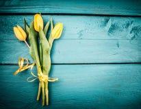 Groupe de tulipes jaunes sur le fond en bois de bleu de turquoise, vue supérieure, endroit pour le texte Photographie stock