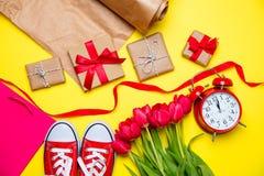 Groupe de tulipes rouges, chaussures en caoutchouc rouges, panier frais, cloc d'alarme Photos stock