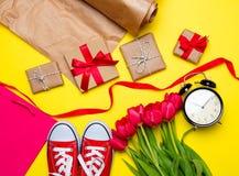 Groupe de tulipes rouges, chaussures en caoutchouc rouges, panier frais, cloc d'alarme Photos libres de droits