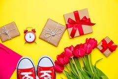 Groupe de tulipes rouges, chaussures en caoutchouc rouges, panier frais, cloc d'alarme Photographie stock