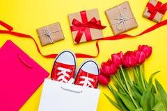 Groupe de tulipes rouges, chaussures en caoutchouc rouges, paniers frais, ruban Images libres de droits