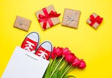 Groupe de tulipes rouges, de chaussures en caoutchouc rouges, de panier frais et de beautif Photographie stock libre de droits