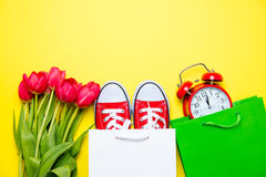 Groupe de tulipes rouges, de chaussures en caoutchouc rouges, de paniers frais et d'alarme Photo stock