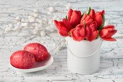 Groupe de tulipes rouges et de deux oeufs de pâques rouges sur le fond blanc Photos stock