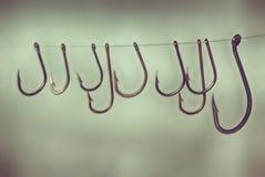 Groupe de vieux hameçons rouillés sur la ligne de pêche plan rapproché léger de fond Photos stock
