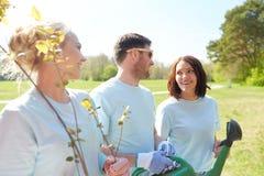 Groupe de volontaires avec des jeunes plantes d'arbre en parc Photos libres de droits