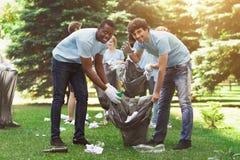 Groupe de volontaires avec des sacs de déchets nettoyant le parc photos stock