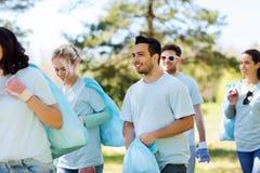 Groupe de volontaires avec des sacs de déchets en parc photo stock