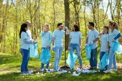 Groupe de volontaires avec des sacs de déchets en parc Images stock
