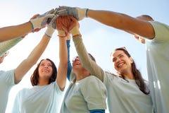 Groupe de volontaires faisant la haute cinq dehors Photographie stock libre de droits