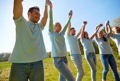 Groupe de volontaires heureux tenant des mains dehors Photos libres de droits
