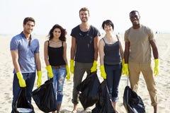 Groupe de volontaires rangeant des déchets sur la plage photos stock