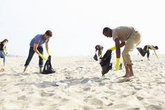 Groupe de volontaires rangeant des déchets sur la plage photographie stock