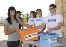 Groupe de volontaires rassemblant des donations de vêtement photos libres de droits