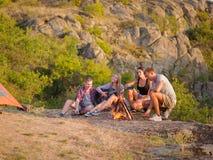 Groupe de voyageurs détendant sur un fond naturel Les amis s'approchent de la cheminée avec une guitare Concept de camping Copiez Image stock