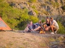 Groupe de voyageurs détendant sur un fond naturel Les amis s'approchent de la cheminée avec une guitare Concept de camping Copiez Photos stock