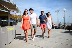 Groupe del hombre y de la mujer de la gente joven que caminan en la playa del centro turístico turístico durante día de verano so Foto de archivo libre de regalías
