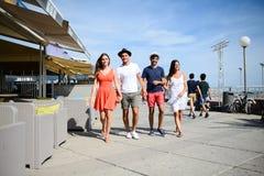 Groupe del hombre y de la mujer de la gente joven que caminan en la playa del centro turístico turístico durante día de verano so Foto de archivo